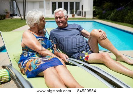 Senior couple interacting with each other on lounge chair at poolside