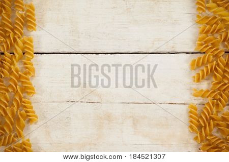Fusilli pasta isolated on wooden table