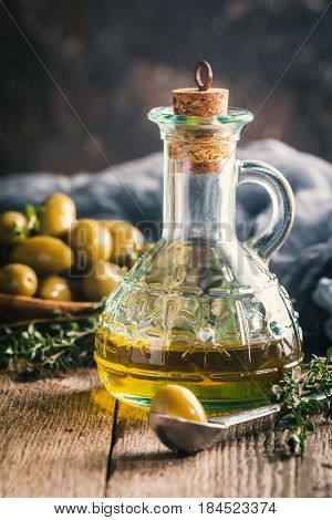 Olive oil and bowl of olives on the wooden table