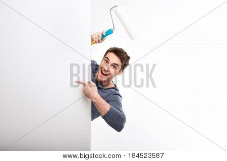 Handsome Man Holding Paint Roller And Pointing On Blank Card Isolated On White, Handyman Tools Conce