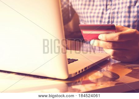 Man using laptop and holding credit card with online shopping or internet banking concept.
