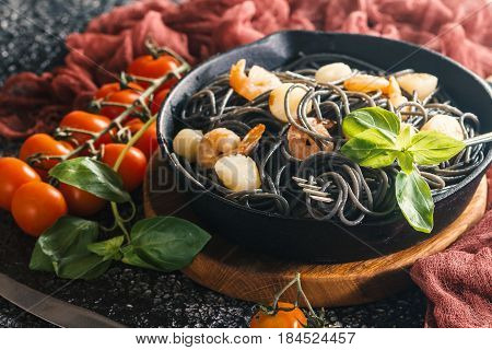 Black spaghetti with prawns and scallop in frying pan on black background