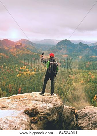 Tourist With Backpack Stayon Cliff And  Takes Photos With Smart Phone Of Rainy Valley.