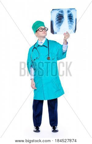 Cute smiling boy dressed like a doctor holding a x-ray. Different occupations. Pediatrics. Isolated over white.