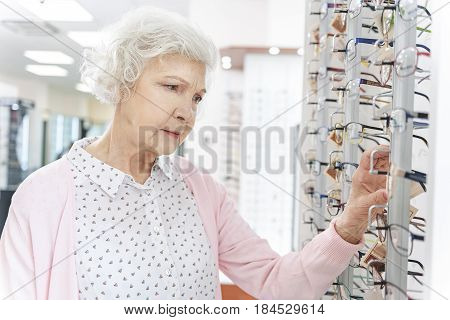 Concentrated old woman is standing near showcase with glasses and looking at eyewear. Portrait