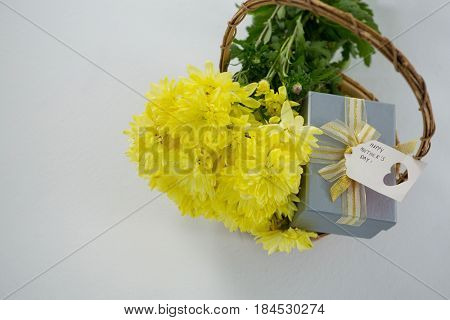 Gift box and bunch of yellow flowers in wicker basket with happy mothers day tag on white background
