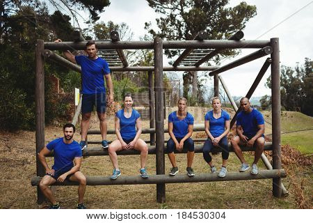 Portrait of fit people sitting on the obstacle couse in bootcamp