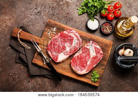 Two Raw fresh meat Ribeye Steakes, seasoning and meat fork on wooden background, top view