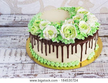 Celebratory cake with roses made of cream on a white wooden background.