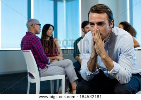 Man crying while creative business team in background at office