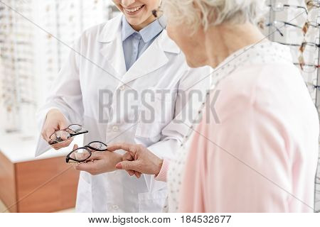 Old woman is choosing liked glasses, female store assistant offering. Focus on female hands holding eyesight