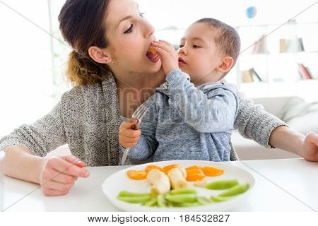 Beautiful Young Mother And Her Son Eating Fruits At Home.