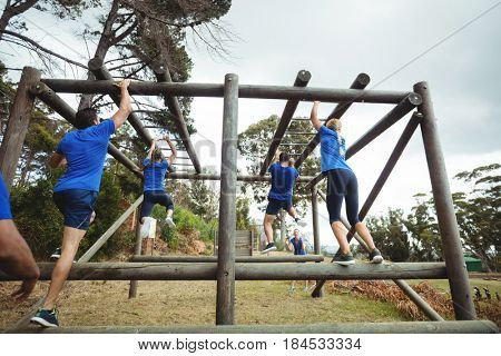 Rear view of fit people climbing monkey bars in bootcamp
