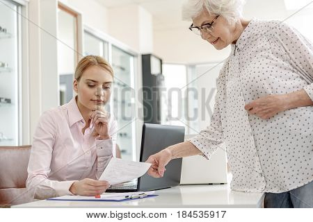 Serious secretary is looking at document, brought by old lady. She standing near countertable. Low angle