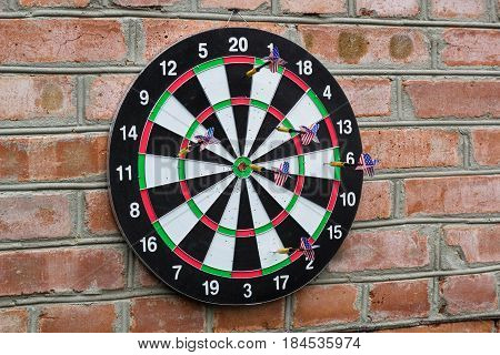 Dart In Bullseye On The Target With Many Other Darts