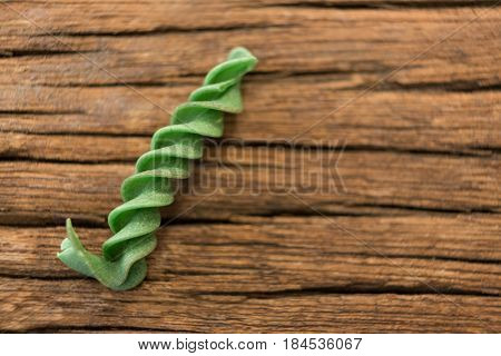 Green rotini isolated on wooden surface