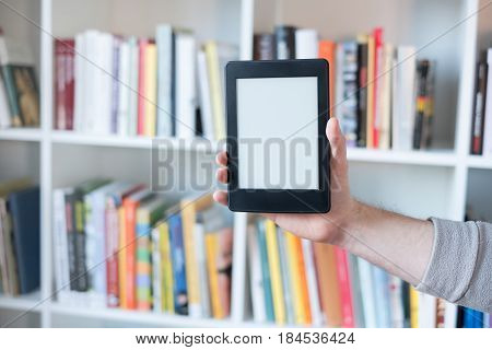 E-book reader and colorful bookshelf on the background