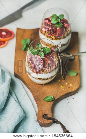 Healthy breakfast. Greek yogurt, granola, blood orange layered parfait in glasses with mint leaves on rustic wooden board over grey marble background. Clean eating, weight loss, detox food concept