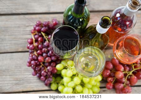 Bunches of various grapes with wine glass and bottles on wooden table