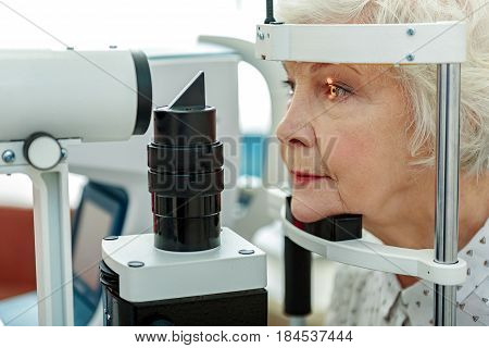 Serious mature lady is putting her head into special optical equipment in order to check her vision. Portrait