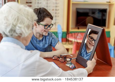 Cheerful child wearing glasses is trying on different variants. Old female oculist holding mirror