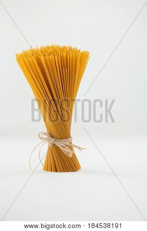 Bundle of raw spaghetti tied with rope on white background