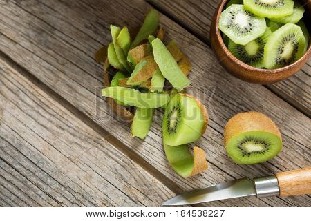 Overhead of slices and pealed kiwi on wooden table