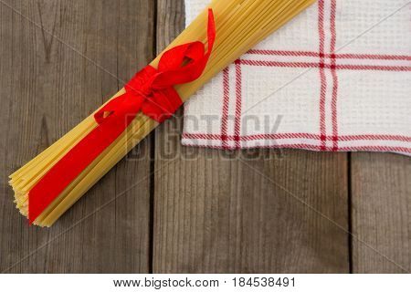 Bundle of raw spaghetti tied with red ribbon on napkin