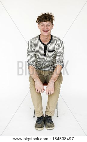 Caucasian man sitting and smiling on white background