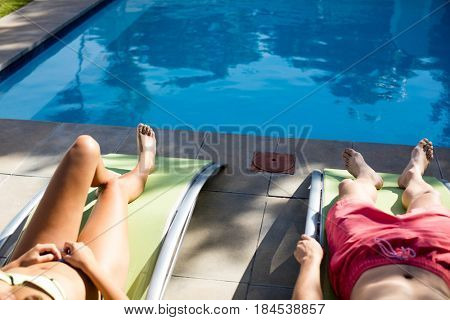 Couple relaxing on lounge chair at poolside on a sunny day