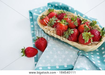 Fresh strawberries in wicker tray on white background