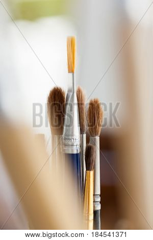 Set of paint brushes in a jar on wooden table