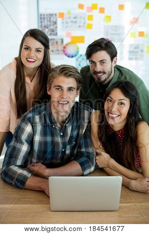 Smiling creative business team discussing over laptop in office