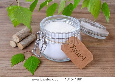 sugar substitute xylitol a glass jar with birch sugar liefs and wood on wooden background
