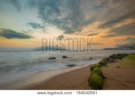 A view of Nha Trang bay just after sunset with moss covered rocks in the foreground and the city lights ablaze.