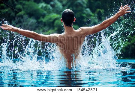 Young swimmer splashing water