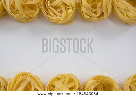 Fettuccine pasta arranged in a row on white background