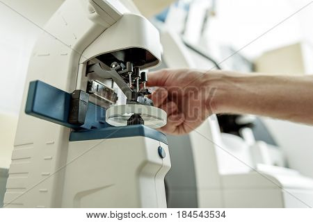 Man is working with special optic equipment. Close up of male hands. Low angle