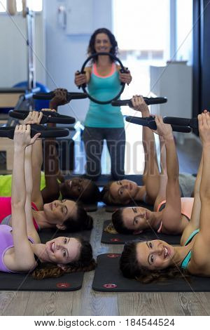 Female trainer assisting group of women with pilates ring exercise in gym