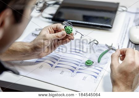 Male person carefully holding glasses an looking at it. Focus on spectacles