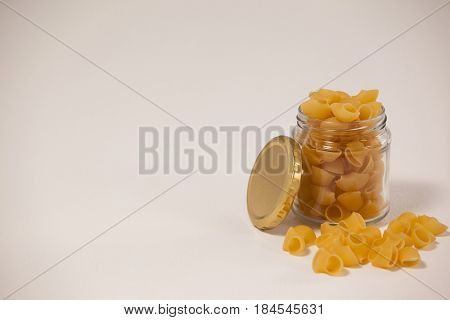 Pipe rigate spilled out of glass jar on wooden background