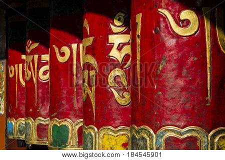 A prayer wheel is a cylindrical wheel  on a spindle made from metal, wood, stone, leather or coarse cotton.  the mantra Om Mani Padme Hum is written in Sanskrit on the outside of the wheel