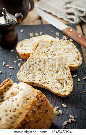Healthy bread with bran sunflower seeds pumpkin flax and sesame seeds on an old wooden background. Top view. Selective focus.
