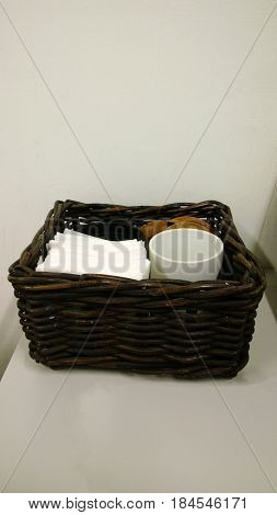 Wooden wicker basket with napkins and cups for a coffee break in the office