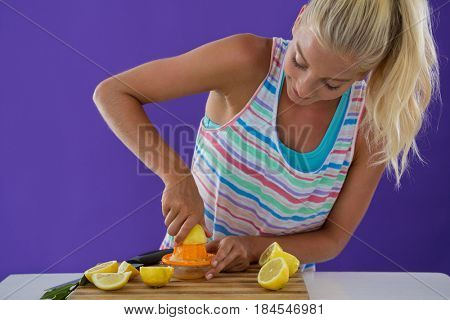 Portrait of woman preparing lemon juice from juicer against violet background