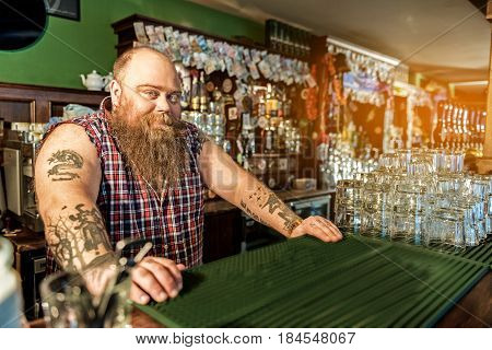 What do you want to order. Portrait of bearded male bartender expressing happiness while standing at counter in beerhouse