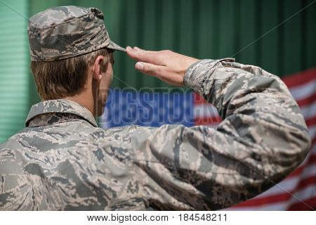 Rear view of military soldier giving salute to american flag in boot camp