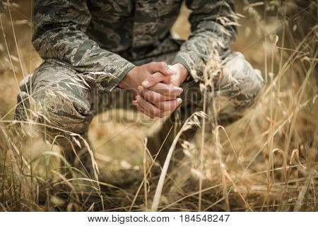 Military soldier crouching in grass in boot camp