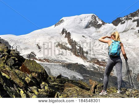 Girl on a trek in the Swiss Alps, in the background mountain Alphubel, Switzerland.