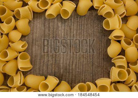 Raw lumache rigate pasta arranged on wooden surface